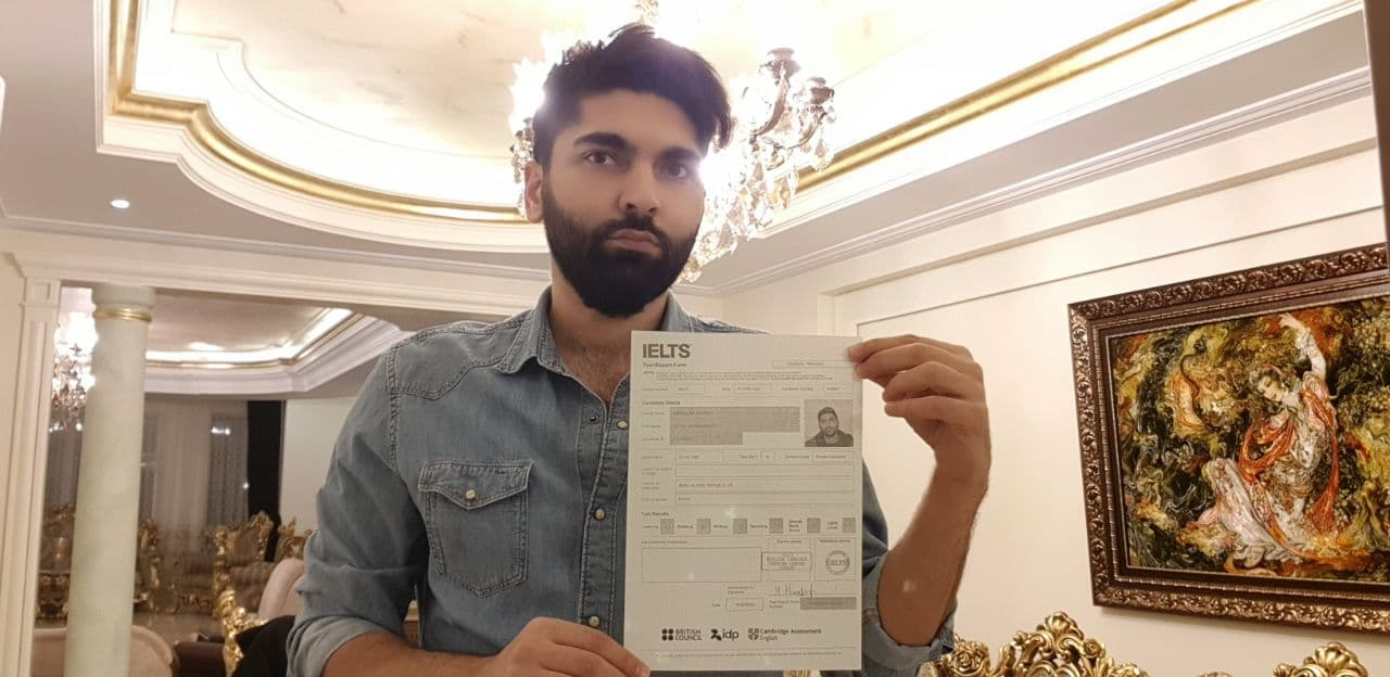 Amirbahador holding his IELTS reports