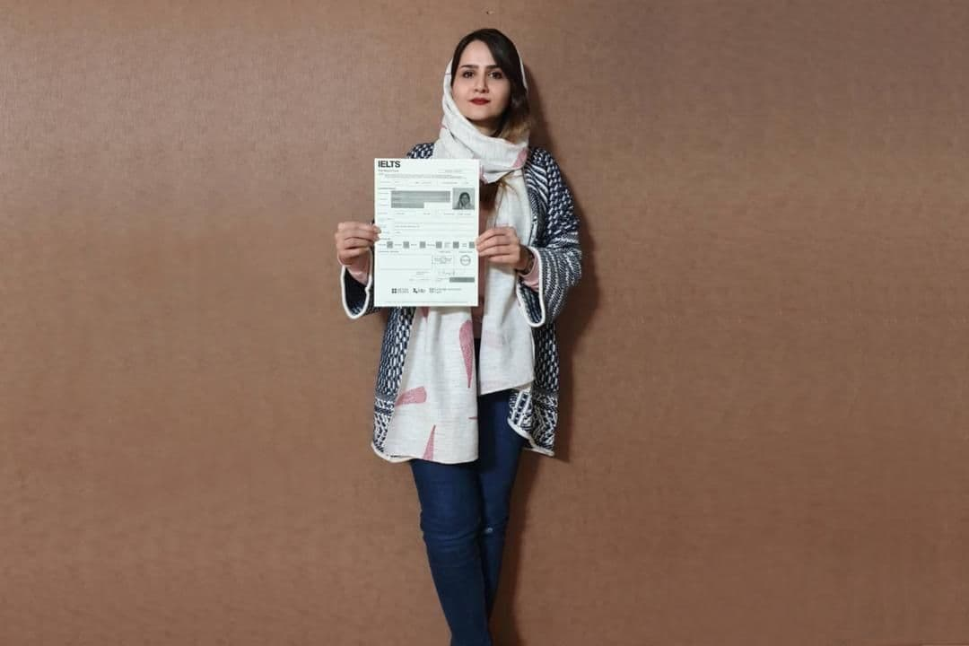 A girl holding her IELTS Sample report